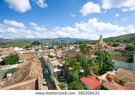 White clouds float in blue sky above the terra cotta rooftops of the historic colonial architecture in the UNESCO heritage center of Trinidad, Cuba - stock photo