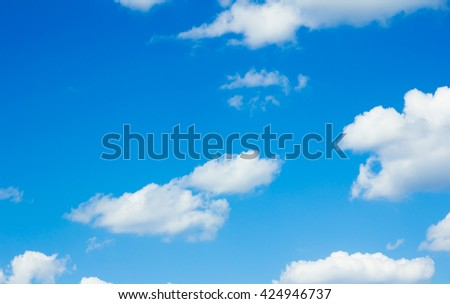White clouds in a bright blue sky. - stock photo