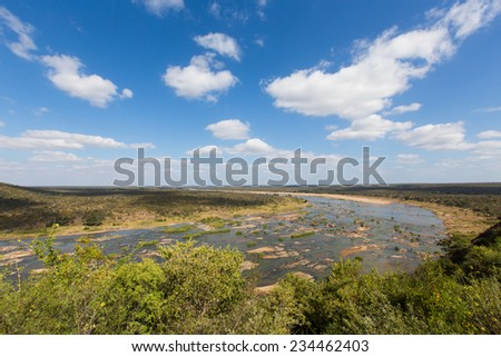 White clouds in a bright blue sky over a bend in the Olifants River in the Kruger National Park, South Africa. - stock photo