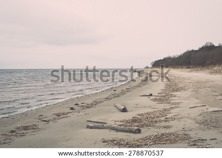 White clouds on the blue sky over country beach - retro vintage grainy film look - stock photo