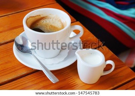 White coffee and milk cups on a wooden cafe table - stock photo