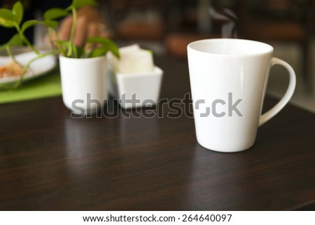 white coffee cup on breakfast wooden desk with copyspace - stock photo