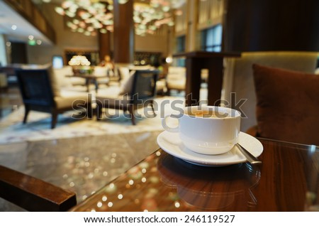 White Coffee cup on the table in lounge bar background. - stock photo