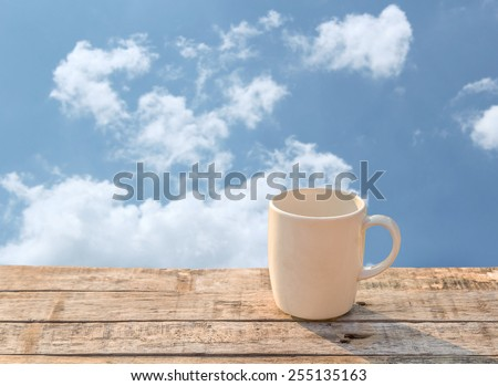 White Coffee cup on wooden table at morning sunlight and blue sky background - stock photo