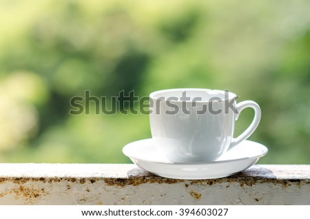 White coffee cup with green bokeh. - stock photo