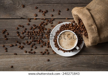 White coffee cup with opened bag. Mug standing on wooden table. - stock photo