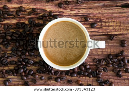 White coffee cup with roasted coffee beans on old wood. - stock photo
