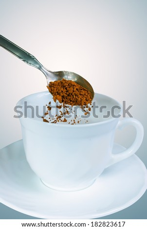 White coffee mug with a teaspoon of granulated instant coffee above the cup  - stock photo