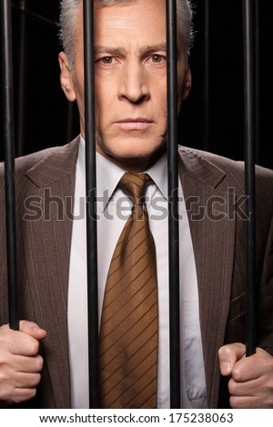 White collar crime. Frustrated senior man in formalwear standing behind a prison cell and looking at camera while isolated on black background  - stock photo