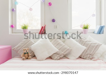 White comfortable sofa with pillows and teddy bear - stock photo
