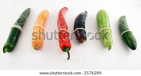 White condoms on different vegetables: pepper, carrot,  egg-plant, cucumber - stock photo