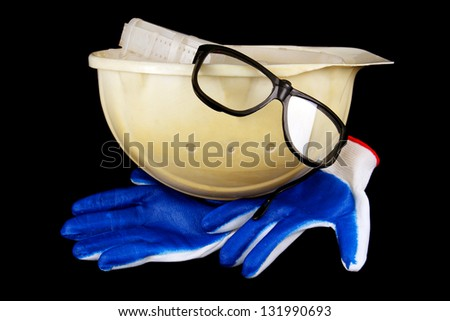 white construction helmet, gloves and goggles isolated on a black background. - stock photo
