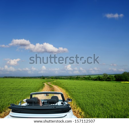 White convertible on a country road - stock photo