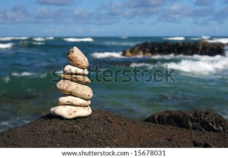 White coral rocks stacked by a meditating zen follower - stock photo
