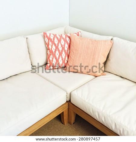 White corner sofa with pink cushions. Modern furniture. - stock photo