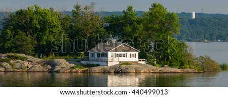 White cottage on a rocky island - stock photo