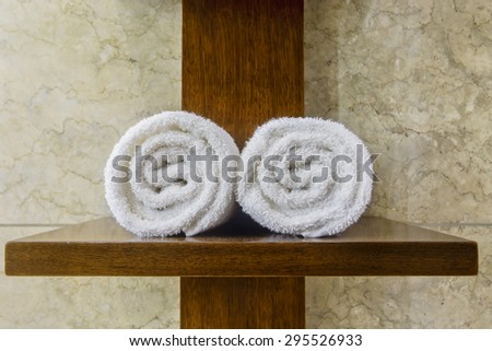 White cotton hotel towels on wooden cross - stock photo