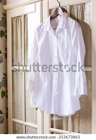 white cotton shirt on a hanger on the door wardrobes - stock photo