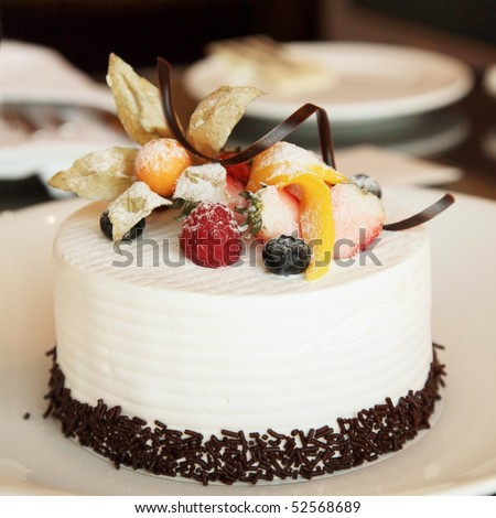 White Cream Icing Cake with Fruits and Chocolate - stock photo