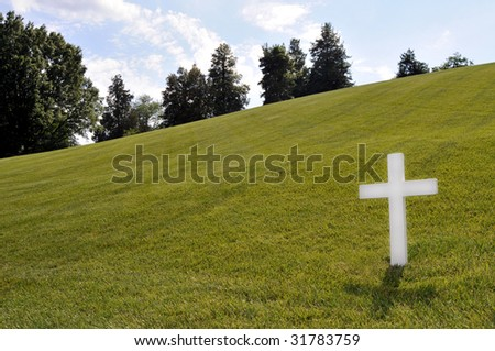 White Cross on a grassy slope at Arlington National Cemetery, with copyspace on left - stock photo