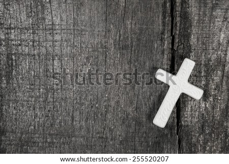 White cross on a grey wooden background. - stock photo