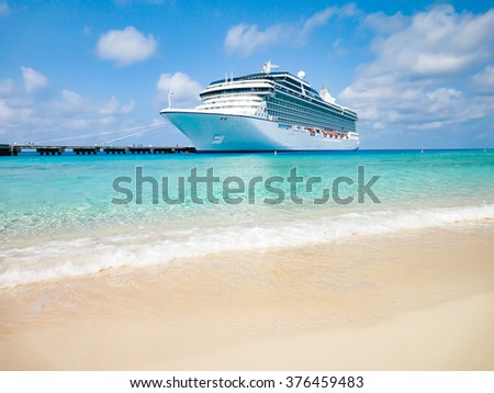 White cruise ship docked at tropical beach in the Caribbean. - stock photo
