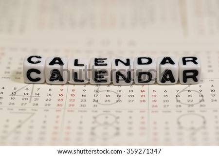 White cube blocks with the text, CALENDAR, on Calendar - stock photo
