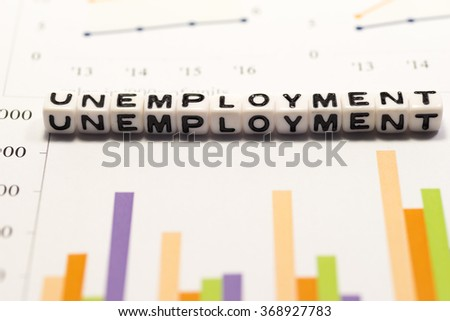 White cube blocks with the text, UNEMPLOYMENT, on graphs - stock photo