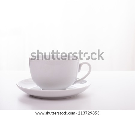 White cup and saucer on a white top with a white background - stock photo