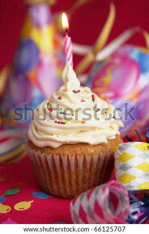 White cup cake with candies on top and candle on red background - stock photo