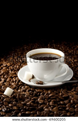 white cup full of coffee and beans - stock photo
