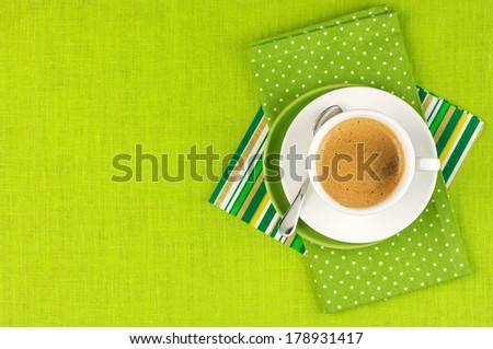 White cup of coffee on green linen. Top view. - stock photo