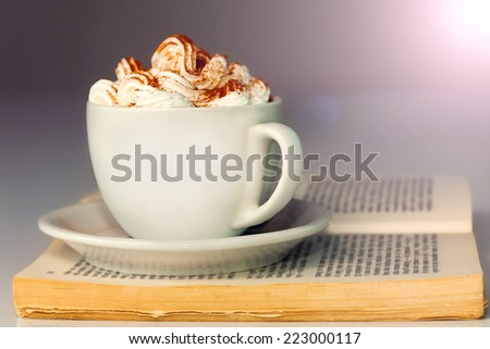 White cup of coffee with cream, on the open book. - stock photo