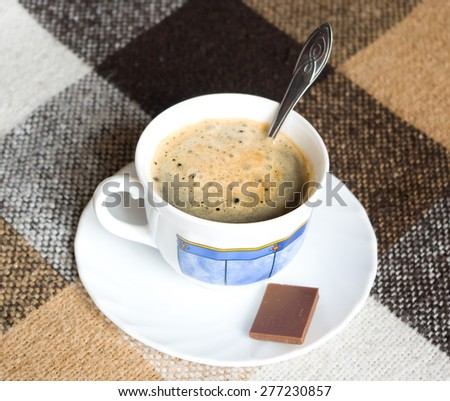 White cup of coffee with piece of milk chocolate on a checkered English plaid - stock photo