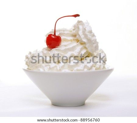 White cup of whipped cream with a red candied cherry on top, on a white background - stock photo