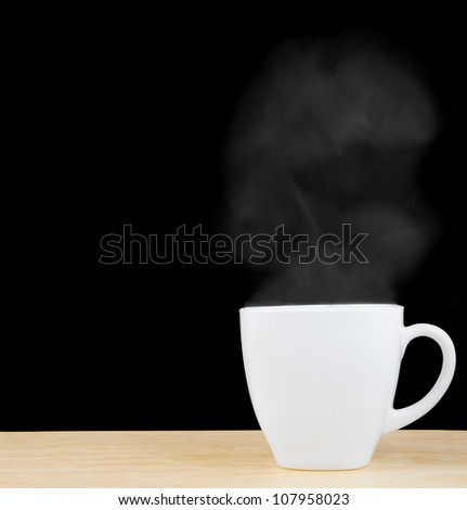 White cup on wooden table with vapor on black - stock photo