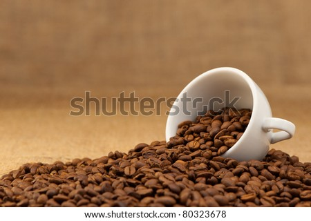 White cup with coffee grains. Grunge background - stock photo