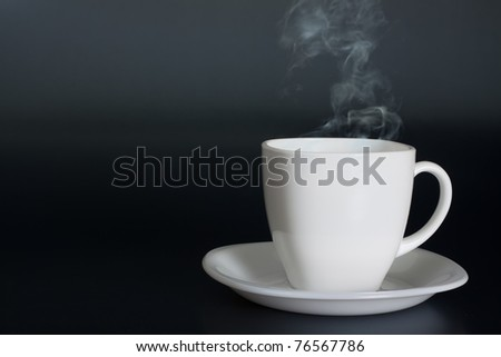 white cup with hot liquid and steam - stock photo