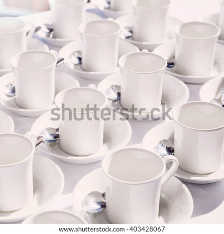 White cups arranged on the table - stock photo