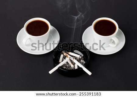 White cups of coffee with ashtray and cigarettes on the black background - stock photo