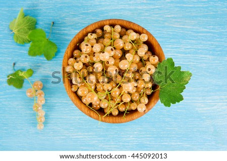 White currant in a wooden bowl. Top view. Ripe and tasty currant isolated on white background. White currants with green leaves.  - stock photo