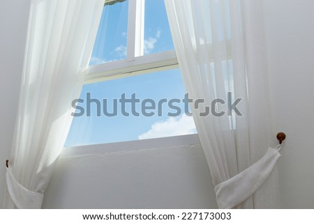 white curtain on the window with blue sky - stock photo