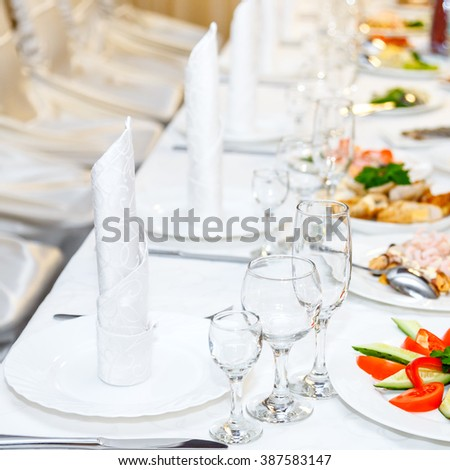 White cutlery and vineglasses on the banquet table. - stock photo
