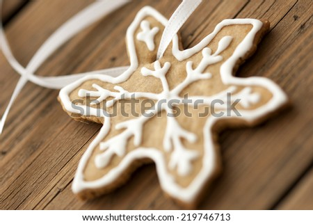 White Decorated Ginger Bread Star Cookie on white Ribbon as Macro as Background on Wood - stock photo