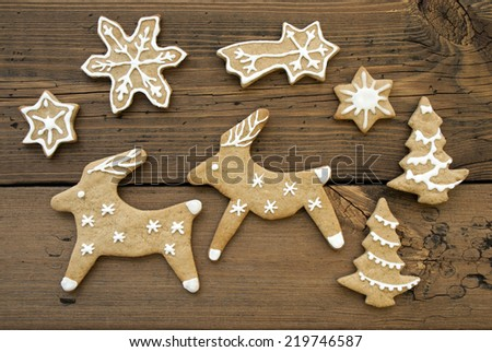White Decorated Ginger Breads, two Reindeers, Stars, Snowflakes and Christmas Trees on Wooden Background - stock photo