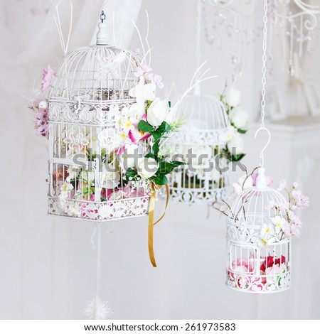 White decorative cage with beautiful flowers, suspension cells - stock photo