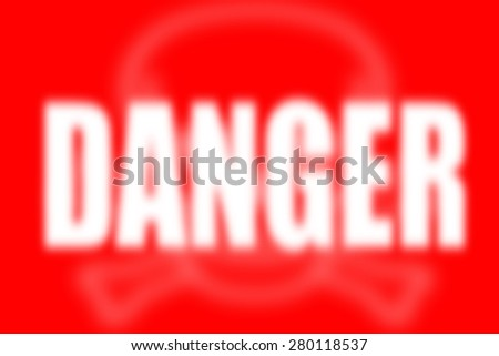 white defocused blur word DANGER on red background with blurred skull sign - stock photo