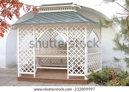 White delicate wooden gazebo in the quiet secluded place, Novospassky monastery, Moscow, Russia. - stock photo