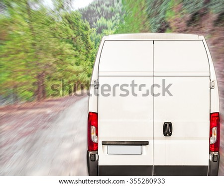 White delivery Van driving fast on forest road - stock photo