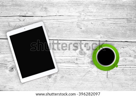 White digital tablet and coffee cup on white wooden table, copy space - stock photo
